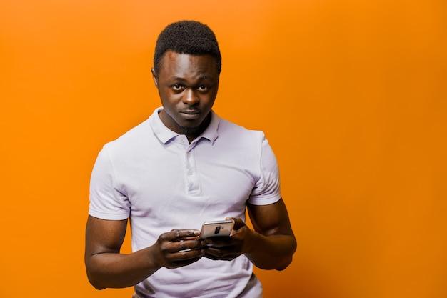 Knappe afrikaanse met telefoon op oranje oppervlak
