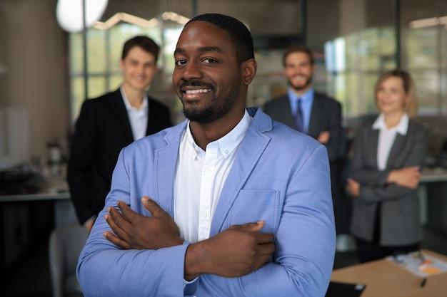 Knappe afrikaanse zakenman met een groep ondernemers op de achtergrond.