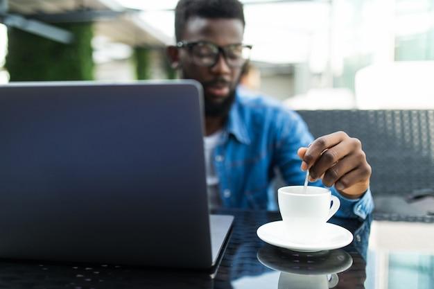 Knappe afrikaanse zakenman met online bijeenkomst op laptop in een café en koffie drinken