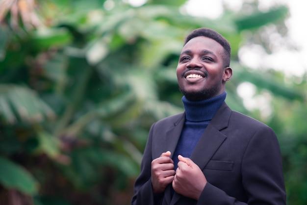 Knappe afrikaanse zakenman permanent in trendy formeel zwart pak. man met baard draagt blauwe lange mouw of trui