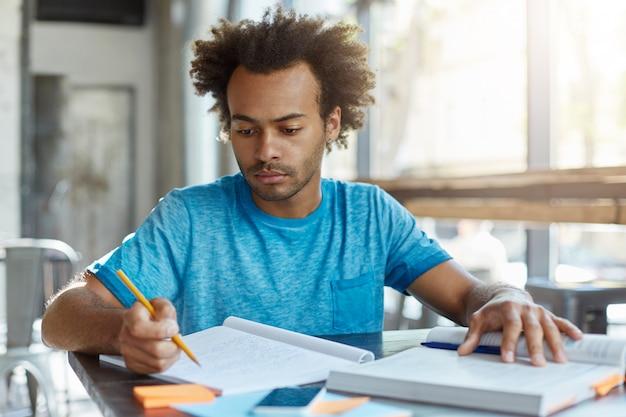 Knappe afro-amerikaanse afgestudeerde student met krullend kapsel zittend aan een bureau met boek en schrift, informatie en notities bestuderen, examen of test voorbereiden, gefocust en geconcentreerd kijken