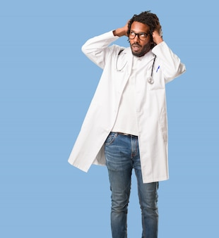 Knappe afro-amerikaanse arts gefrustreerd en wanhopig, boos en verdrietig met de handen op het hoofd