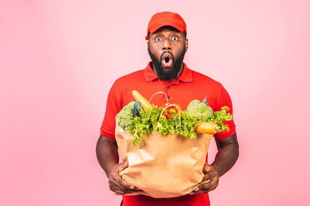 Knappe afro-amerikaanse bezorger met pakket doos met kruidenier voedsel uit de winkel