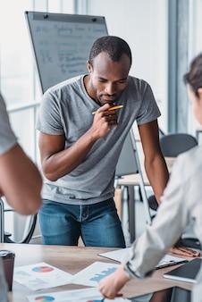 Knappe afro-amerikaanse man die bij het bureau staat en nadenkt over een nieuw zakelijk project
