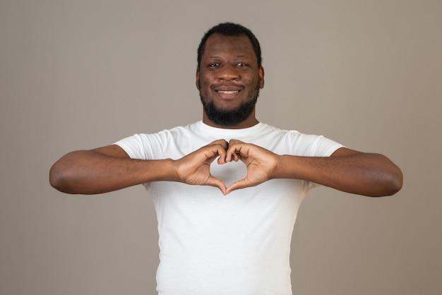 Knappe afro-amerikaanse man die een hart maakt met zijn handen, staat over een beige muur.
