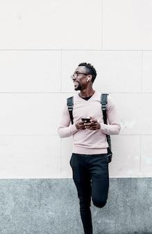Knappe afro-amerikaanse man die lacht met smartphone