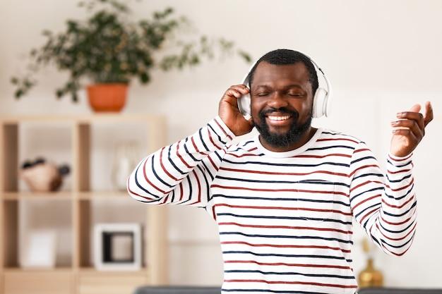 Knappe afro-amerikaanse man die thuis naar muziek luistert