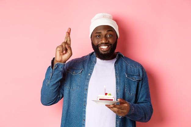 Knappe afro-amerikaanse man die verjaardag viert, wens doet met gekruiste vingers, verjaardagstaart met kaars vasthoudt, staande tegen roze achtergrond