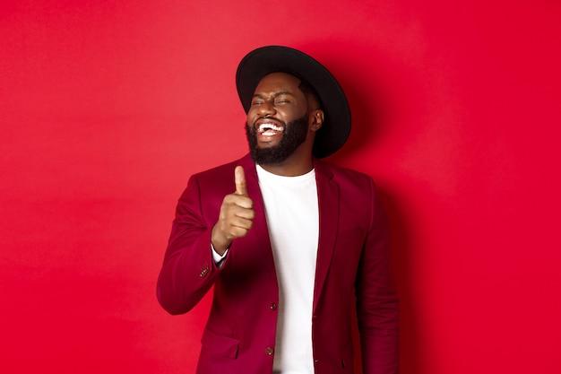 Knappe afro-amerikaanse man met plezier, duim opdagen en lachen van goede grap, staande tegen rode achtergrond.