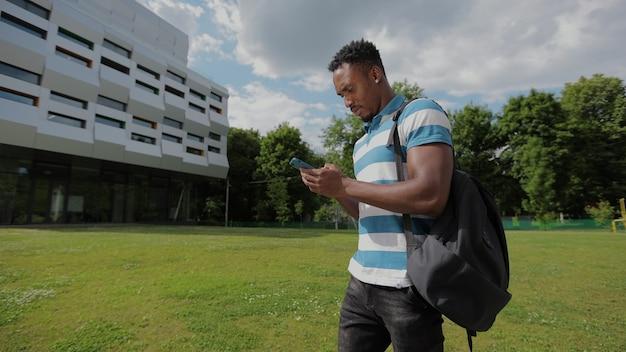 Knappe afro-amerikaanse man met smartphone op de achtergrond van de universiteit afro-amerikaanse man leest en typt een bericht op de telefoon met een app die lacht, gelukkig staat hij in de buurt van het kantoorcentrum