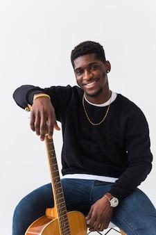 Knappe afro-amerikaanse man poseren in zwart sweatshirt met gitaar