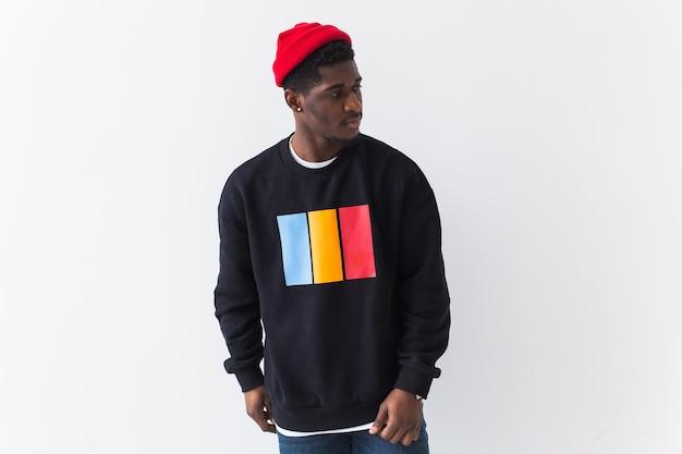 Knappe afro-amerikaanse man poseren in zwart sweatshirt op een wit