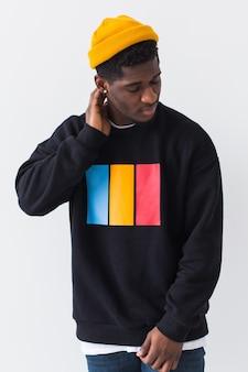 Knappe afro-amerikaanse man poseren in zwart sweatshirt op een witte achtergrond. straatmode voor jongeren