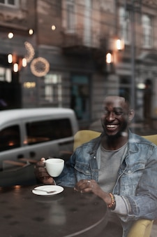 Knappe afro-amerikaanse mens die middelgroot schot glimlacht
