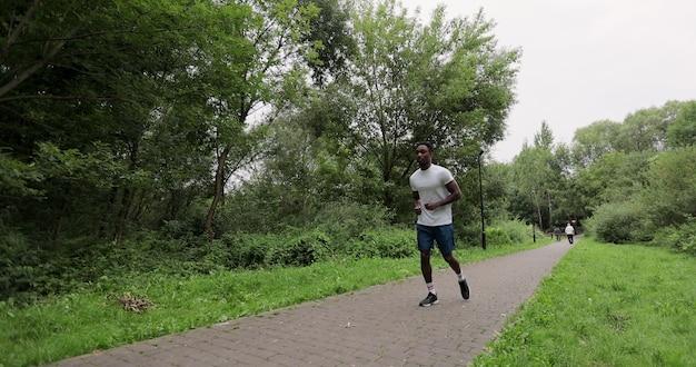 Knappe afro-amerikaanse sporter die buitenshuis in slow motion traint. een man in sportkleding rent tussen de bomen in het park. concept van gezonde levensstijl.