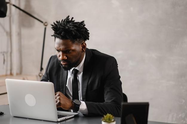 Knappe afro-amerikaanse zakenman in klassiek pak gebruikt laptop en glimlacht terwijl hij op kantoor werkt