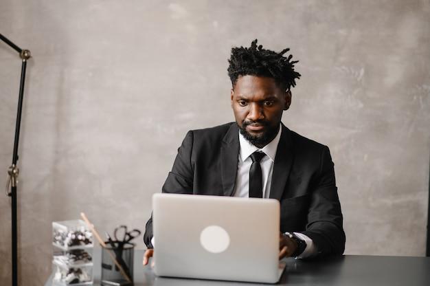 Knappe afro-amerikaanse zakenman in klassiek pak gebruikt laptop