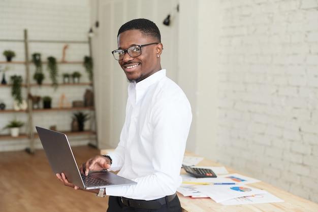 Knappe afro-amerikaanse zakenman in overhemd en broek maakt gebruik van laptop en maakt aantekeningen