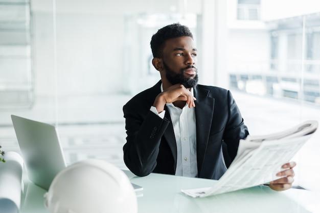 Knappe afro-amerikaanse zakenman met krant in de buurt van business center kantoor