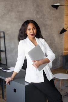 Knappe afro-amerikaanse zakenvrouw in klassiek pak maakt gebruik van laptop en glimlacht tijdens het werken op kantoor