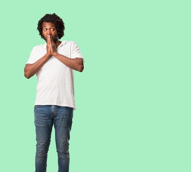 Knappe afro-amerikaanse zeer bang en bang, wanhopig op zoek naar iets, huilt van lijden en open ogen, concept van waanzin