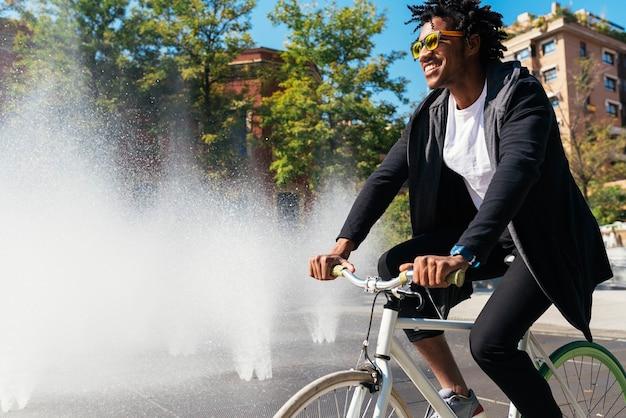 Knappe afro man op een fiets in de straat.