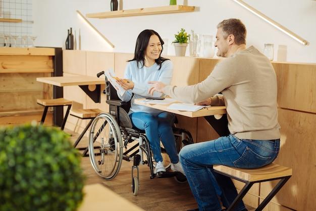 Knappe, alerte, donkerharige, kreupele vrouw en een vrolijke, goedgebouwde blonde man die samen in een café zitten en glimlachen en werk bespreken