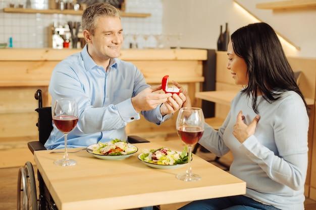 Knappe, alerte gehandicapte man die lacht en zijn aantrekkelijke geliefde tevreden vrouw voorstelt en een ring vasthoudt tijdens een romantisch diner