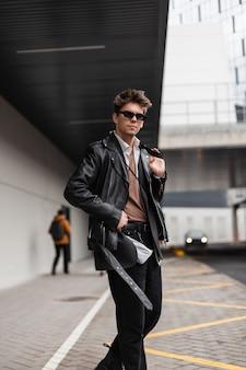 Knappe amerikaanse jongeman in een stijlvolle oversized leren zwarte jas in stijlvolle zonnebril in vintage jeans loopt door de straat in de stad. aantrekkelijke trendy hipster man staat in de buurt van grijs gebouw