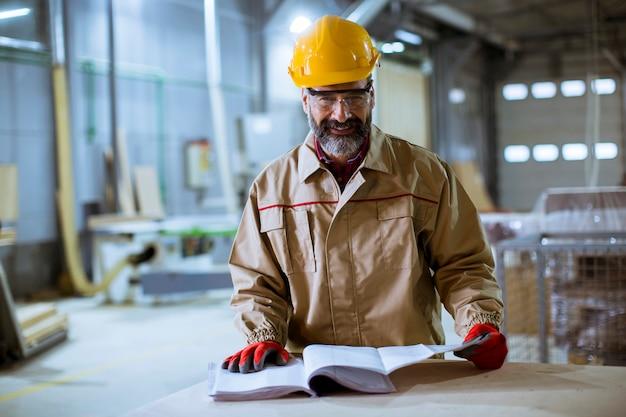 Knappe arbeider van middelbare leeftijd die documentatie in de fabriek controleert