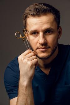Knappe arts met chirurgische schaarclose-up. zelfverzekerde man medische apparatuur in handen houden en glimlachen.