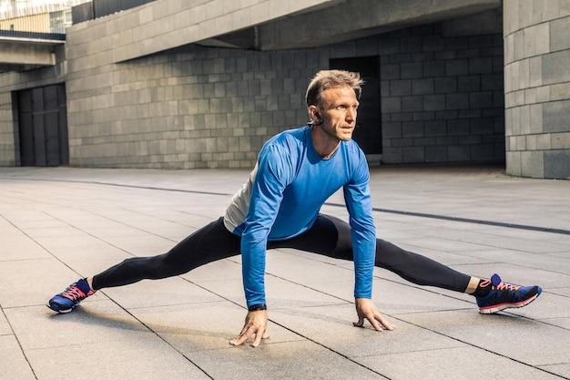 Knappe atleet man in zwart blauw sport uniform lichaam uitrekken, opwarmen en maak je klaar om te joggen.