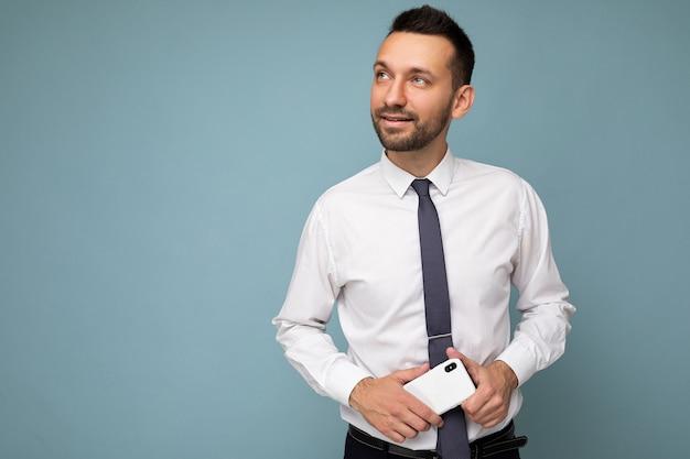 Knappe attente knappe brunet ongeschoren man met baard met casual wit overhemd en stropdas