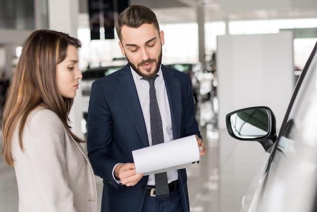 Knappe autoverkoper praten met klant