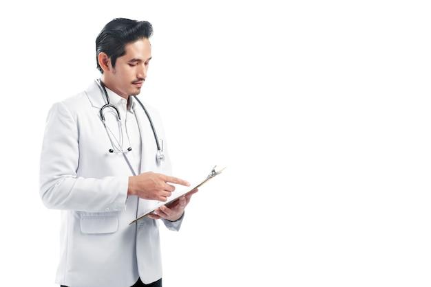 Knappe aziatische artsenmens die de notas van de laboratoriumlaag op het klembord lezen