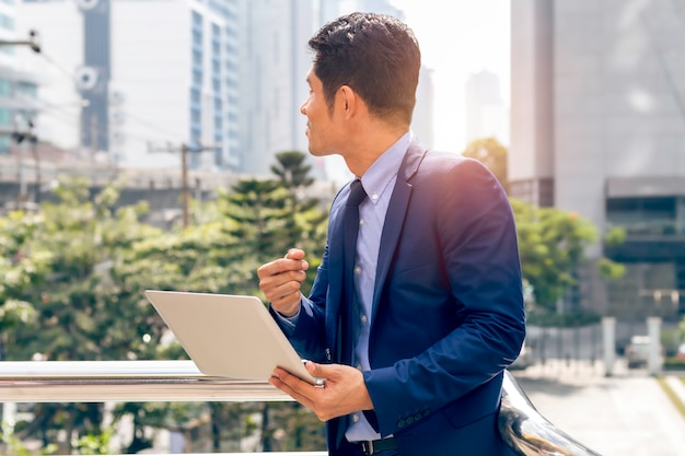 Knappe aziatische bedrijfsleidermens die en zich met laptop bevinden werken bij de openluchtstad.