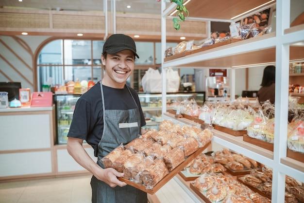 Knappe aziatische lachende werknemer bij de bakkerijwinkel met een dienblad met brood