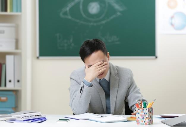 Knappe aziatische leraar zit in de klas
