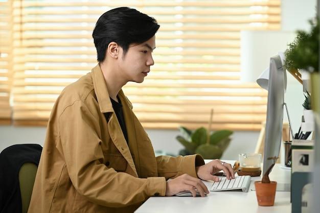 Knappe aziatische man aan het werk met computer in kantoor aan huis.