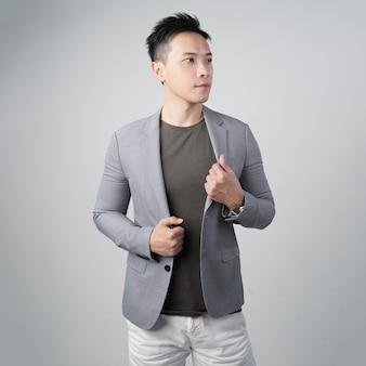 Knappe aziatische man aanpassen pak geïsoleerde grijze muur