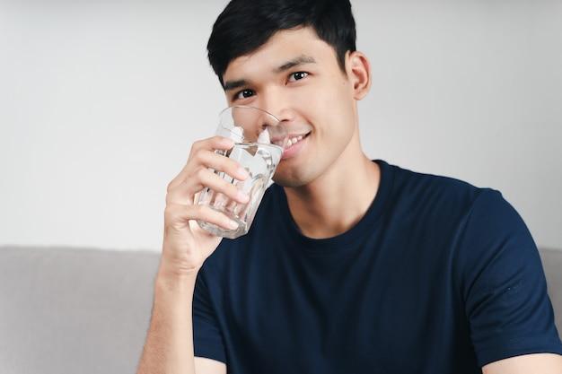 Knappe aziatische man die een glas water drinkt op de bank in de woonkamer