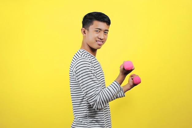 Knappe aziatische man die lacht om gewichtheffen te doen, oefeningen te doen met dumbell, gezonde levensstijl, sporttrainingsconcept, gele achtergrond