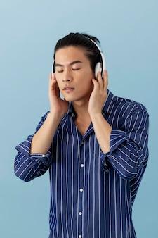 Knappe aziatische man die naar muziek luistert via een koptelefoon
