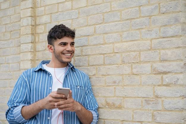 Knappe aziatische man met behulp van mobiele telefoon, muziek buitenshuis luisteren