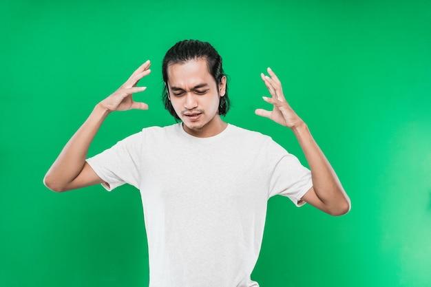 Knappe aziatische man met een verwarde uitdrukking op het gezicht terwijl hij twee handen aan de zijkant van het hoofd opheft, geïsoleerd op de groene muur