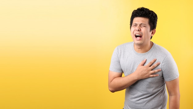 Knappe aziatische man met hartpijn, op gele muur.
