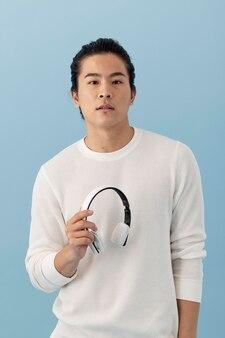 Knappe aziatische man met koptelefoon