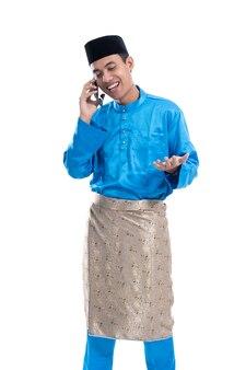 Knappe aziatische mannelijke moslim praten over zijn telefoon op witte achtergrond