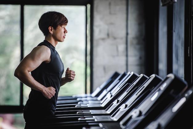 Knappe aziatische mannen oefenen in sportkleding en joggen op de loopband in de sportschool. elektrische loopband in het fitnesscentrum