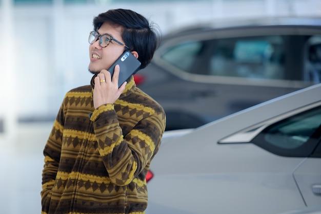 Knappe aziatische mannen zijn blij om een nieuwe auto in de showroom te kopen, blij tijdens het praten aan de telefoon, enthousiast over het goede nieuws online in de showroom.